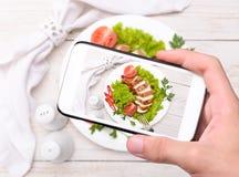 Manos que toman la pechuga de pollo de la foto con smartphone Foto de archivo libre de regalías