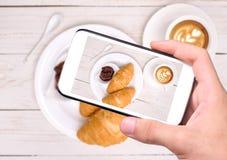 Manos que toman la taza de la foto de café con los cruasanes con smartphone Fotos de archivo