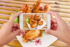 Manos que toman las alas de pollo de la foto con smartphone Foto de archivo libre de regalías