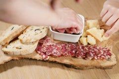 Manos que toman los aperitivos italianos de los antipasti en la tabla Fotos de archivo libres de regalías