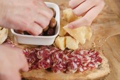 Manos que toman los aperitivos italianos de los antipasti en la tabla Fotografía de archivo