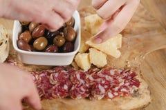 Manos que toman los aperitivos italianos de los antipasti en la tabla Foto de archivo