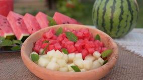 Manos que toman los cubos de la sandía y del melón de una placa Ensalada de fruta de restauración del verano cerca para arriba metrajes