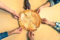 Manos que toman rebanadas de la pizza Imagen de archivo