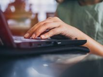 Manos que trabajan con el teclado en el ordenador portátil negro imágenes de archivo libres de regalías