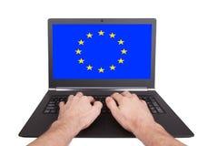 Manos que trabajan en el ordenador portátil, unión europea Imagen de archivo libre de regalías