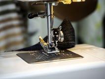 Manos que trabajan en la máquina de coser fotografía de archivo