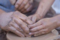 Manos que trabajan en la rueda de la cerámica Foto de archivo libre de regalías