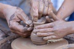 Manos que trabajan en la rueda de la cerámica Imágenes de archivo libres de regalías
