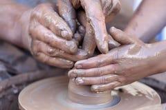 Manos que trabajan en la rueda de la cerámica Imagen de archivo libre de regalías