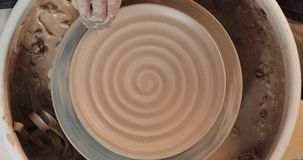 Manos que trabajan en la rueda de la cerámica con las herramientas profesionales, formando un alivio en una placa de la arcilla V almacen de metraje de vídeo