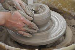 Manos que trabajan en la rueda de la cerámica Fotografía de archivo libre de regalías