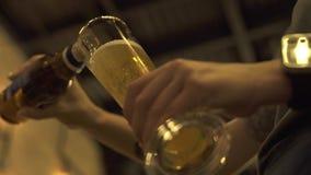 Manos que vierten la cerveza de la botella en vidrio en barra del pub, restaurante o cierre del café para arriba Manos del camare almacen de metraje de vídeo