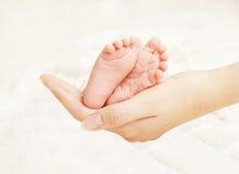 Manos recién nacidas de la madre de los pies del bebé Pie recién nacido del niño, amor de la familia Imagen de archivo
