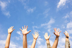 Manos rised para arriba en aire a través del cielo Fotografía de archivo