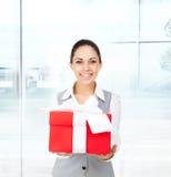 Manos rojas de la caja de regalo del control de la sonrisa de la mujer de negocios Imagen de archivo