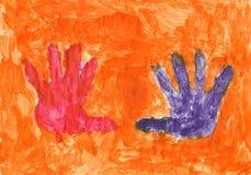 Manos rojas y violetas en el fondo anaranjado Fotografía de archivo libre de regalías