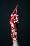 Manos sangrientas en los guantes blancos, un escalpelo, un clavo, fondo negro, zombi, demonio, maniaco Fotografía de archivo libre de regalías