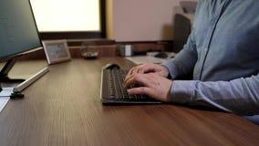 Manos significativas del hombre en una camisa azul que mecanografía en el teclado Escritura de un documento en software de la ofi almacen de metraje de vídeo