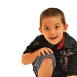 Manos sonrientes del whth del muchacho en rodilla Foto de archivo libre de regalías