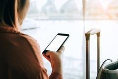 Manos turísticas asiáticas de la mujer que sostienen y que usan smartphone con vuelo que espera de la pantalla en blanco para en  fotografía de archivo libre de regalías