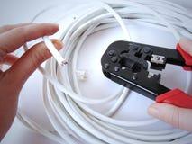 Manos usando el arrugador del cable Foto de archivo libre de regalías