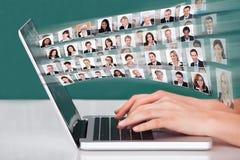 Manos usando el ordenador portátil con collage de los empresarios Foto de archivo libre de regalías