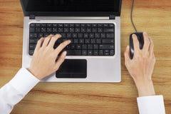 Manos usando el ordenador portátil y el ratón Fotos de archivo libres de regalías