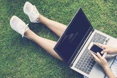 Manos usando el ordenador portátil y el smartphone en hierba verde Imagen de archivo