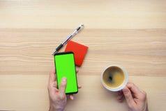 Manos usando el teléfono elegante y observación abajo en notas pegajosas Foto de archivo libre de regalías