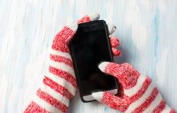 Manos usando el teléfono en guantes del invierno imagenes de archivo