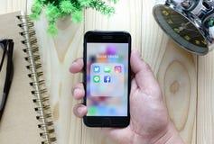 Manos usando Iphone7 con los iconos del uso Imagen de archivo