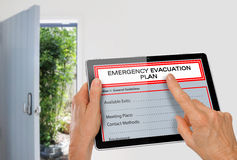 Manos usando la tableta con el plan de evacuación de la emergencia al lado de la puerta de salida Fotografía de archivo