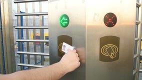 Manos usando las tarjetas plásticas para incorporar el sistema del acceso en la fábrica de la planta almacen de metraje de vídeo