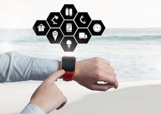 Manos usando smartwatch con los iconos digital generados Foto de archivo