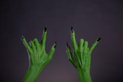 Manos verdes del monstruo que muestran gesto de metales pesados Imágenes de archivo libres de regalías