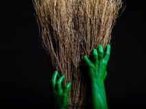 Manos verdes del zombi con una escoba Un Web de araña grande antes de una luna brillante extraña Fotos de archivo libres de regalías