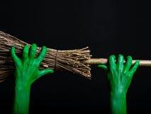 Manos verdes del zombi con una escoba Un Web de araña grande antes de una luna brillante extraña Imágenes de archivo libres de regalías