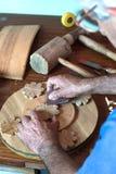 Manos verticales del ebanista del retrato usando el papel de lija en un pedazo de madera Fotos de archivo libres de regalías