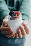 Manos verticales del muchacho de la foto con el pudín con las semillas del chia, yogur Fotos de archivo
