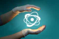 Manos y átomo foto de archivo libre de regalías