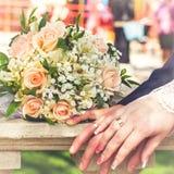 Manos y anillos en ramo de la boda Imagen de archivo libre de regalías