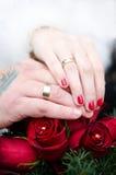 Manos y anillos en ramo de la boda Foto de archivo