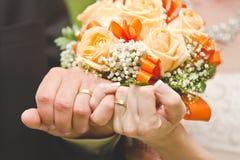 Manos y anillos en ramo de la boda Fotografía de archivo libre de regalías