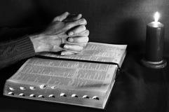 Manos y biblia de rogación con la vela Imagen de archivo libre de regalías