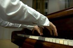 Manos y brazos en el piano Fotografía de archivo libre de regalías