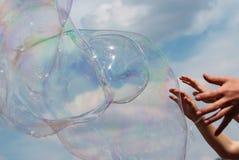 Manos y burbujas contra el cielo Imagenes de archivo