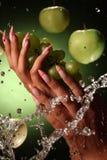 Manos y clavos hermosos en fondo verde Imagen de archivo libre de regalías