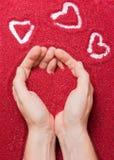 Manos y corazones rojos Fotos de archivo libres de regalías