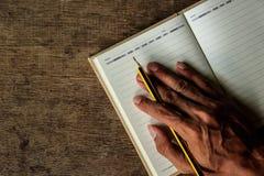 Manos y cuaderno Imagen de archivo libre de regalías